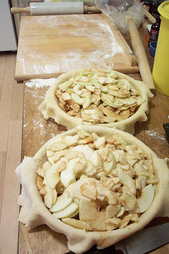 Two apple pies in prep. Board and rolling pin in background.