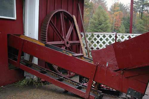 Red conveyor belt going into a red barn.